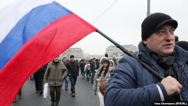 A man carrying a Russian flag walks to a demonstration on Moscow's Bolotnaya Square on December 10.