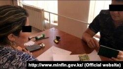 Mangistau regiony. Gazak resmisi saklanan aýalyň dokumentlerini barlaýar.