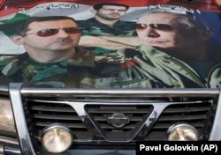 Портреты Владимира Путина и Башара Асада на капоте автомашины в Сирии