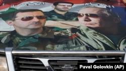 O mașină acoperită cu un colaj prezentîndu-i pe președinții Putin și Assad