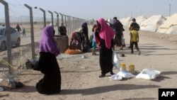 Displaced Iraqis from the embattled city of Fallujah carry bags of food provided by the World Food Program at a camp where they are taking shelter on June 10 some 30 kilometers south of the city.