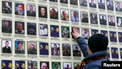A woman touches a portrait of her husband in Kyiv, on a banner with portraits of Ukrainian servicemen killed in the conflict with pro-Russian separatists in eastern Ukraine.