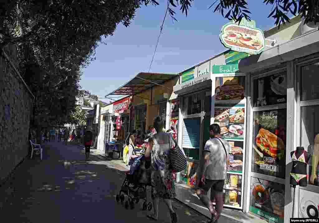 Магазинчики построены на набережной Массандровского пляжа, между домами, имевшими некогда вид на море и собственно пляжем.