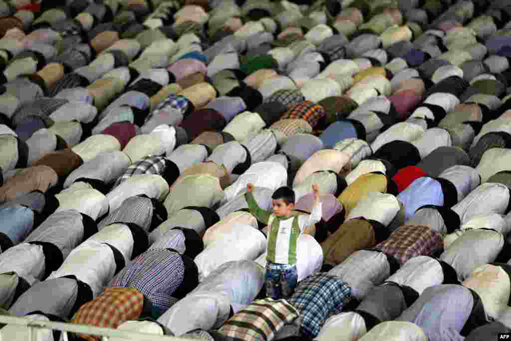 A young boy stands among Shi'ite Muslim worshippers attending the weekly Friday Prayers during the Muslim fasting month of Ramadan at Tehran University. (AFP/Atta Kenare)