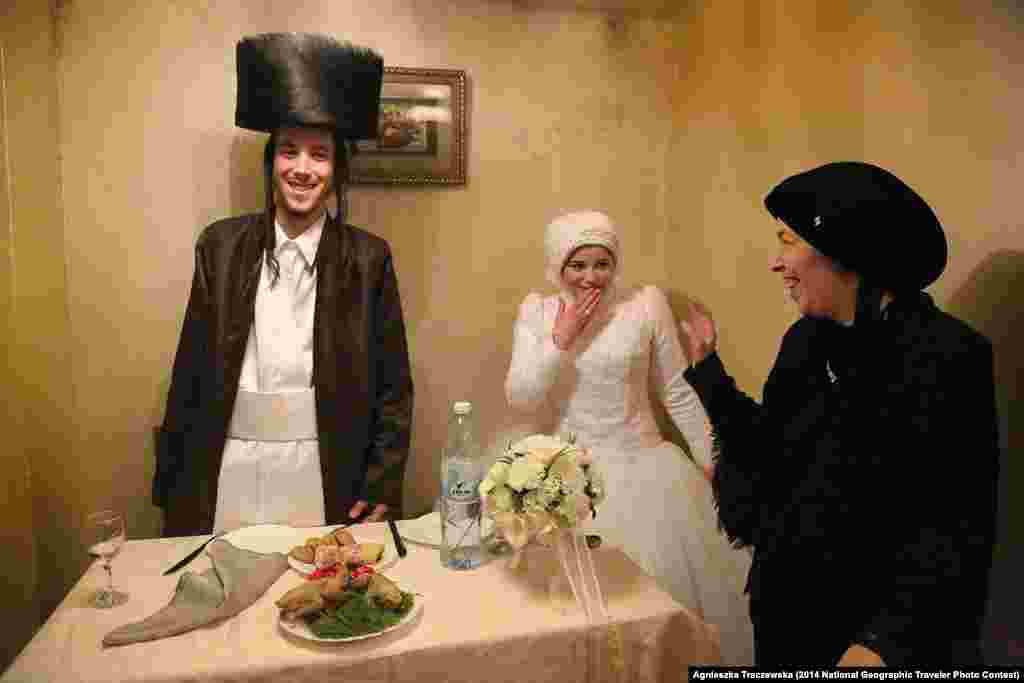 "Second Place: ""First Time"" by Agnieszka Traczewska. Mea Shearim, Jerusalem, Israel.  ""Mea Shearim, Ultra-Orthodox district of Jerusalem. Newly married, Aaron and Rivkeh after the wedding ceremony are to stay together for the very first time, alone. Their marriage was arranged by families. 18 years old candidates confirmed the choice in result of the one meeting only. Since then until the wedding day they were prohibited to meet or even talk."""