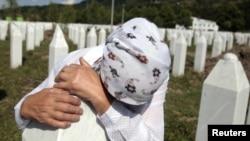 Адила Сулякович Сребреница қырғыны барысында өлтірілген ұлының қабірінде жылап тұр. 3 шілде 2011 жыл.