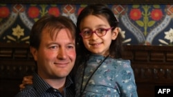 Richard Ratcliffe, husband of British-Iranian aid worker Nazanin Zaghari-Ratcliffe jailed in Tehran since 2016, holds his daughter Gabriella during a news conference in London, on October 11, 2019. - The five-year-old daughter of a British-Iranian woman j