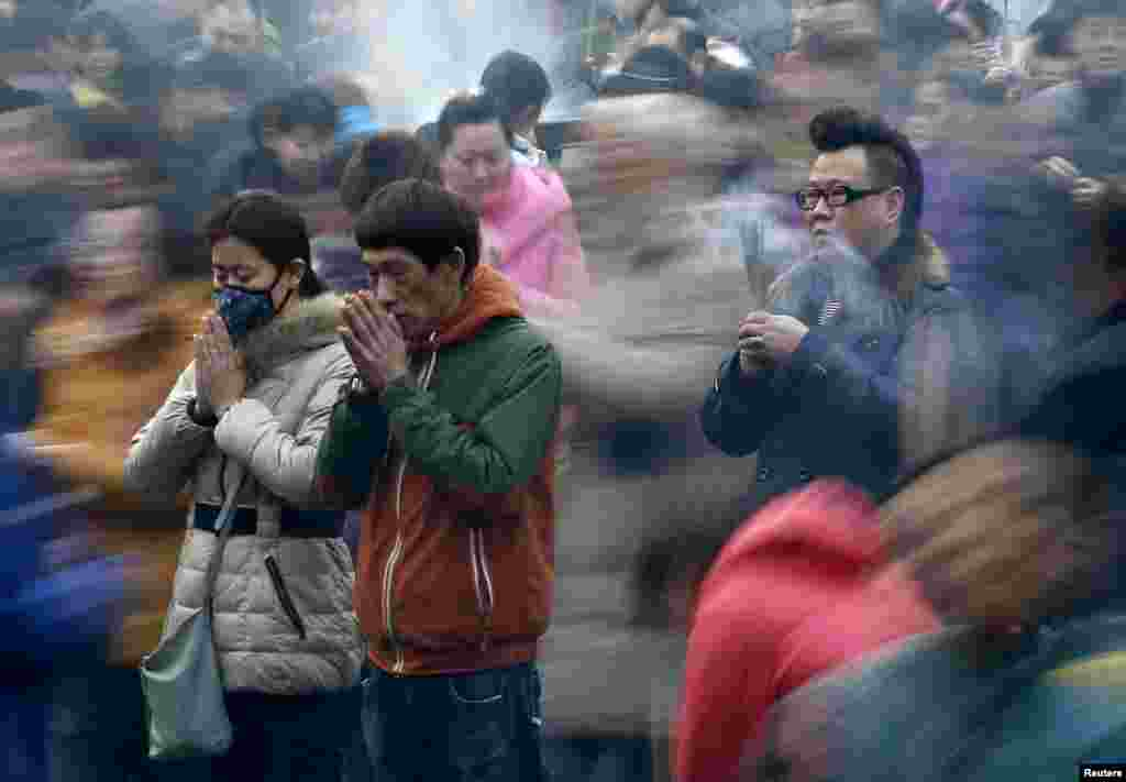 People pray for good fortune on the first day of the Chinese Lunar New Year at Yonghegong Lama Temple, in Beijing, on February 19. (Reuters/Kim Kyung-Hoon)