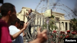 Egypt - A protester standing on a barricade, shouts in front of soldiers outside the Supreme Constitutional Court in Cairo, 14Jun2012