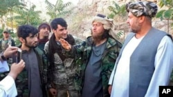 A foreign Islamic State group fighter (2nd right) speaks to a journalist after he surrendered to government security forces in the Darzab district on August 1.