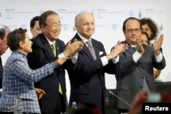 (Left to right:) Christiana Figueres, executive secretary of the UN Framework Convention on Climate Change, United Nations Secretary-General Ban Ki-moon, French Foreign Affairs Minister Laurent Fabius, and French President Francois Hollande applaud during the final plenary session at the World Climate Change Conference 2015, which approved a new environmental agreement in Paris on December 12.