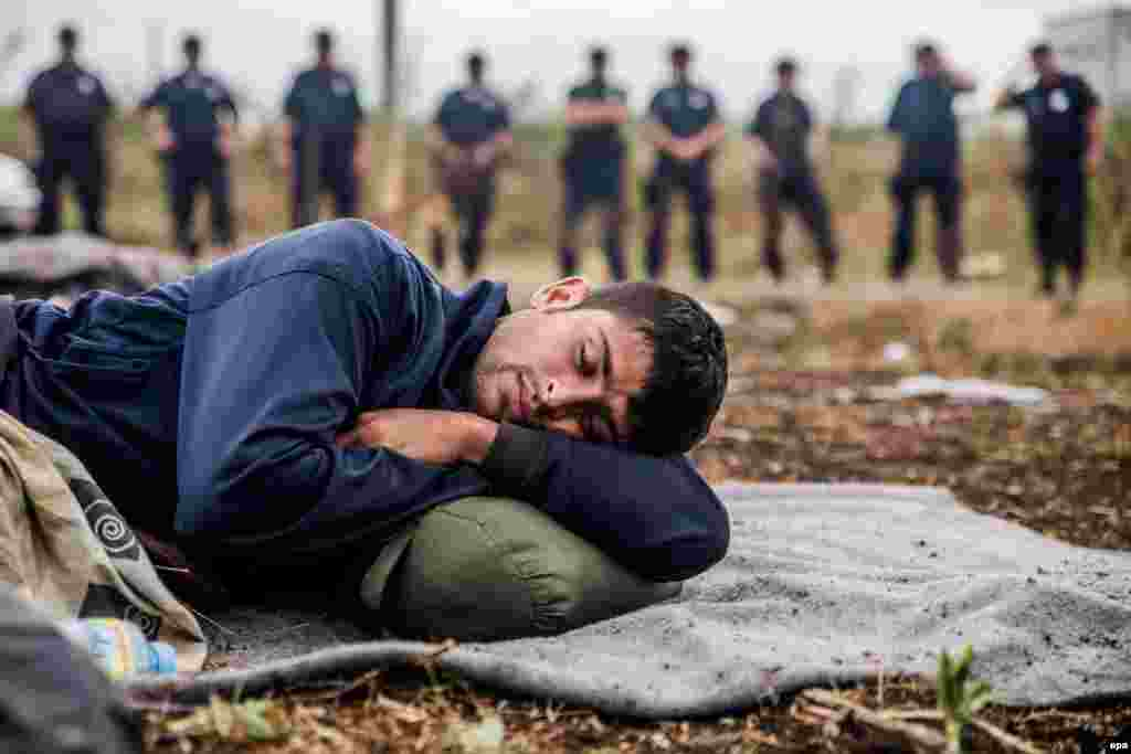 One of several migrants who are on hunger strike to pressure the Hungarian government to open its borders sleeps at the frontier with Serbia in Horgos on July 26. (epa/Zoltan Balogh)