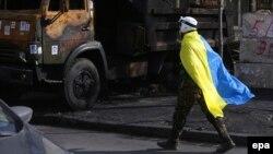 Участник протеста проходит мимо сгоревшего рядом с правительственным зданием грузовика. 24 февраля 2014 года.