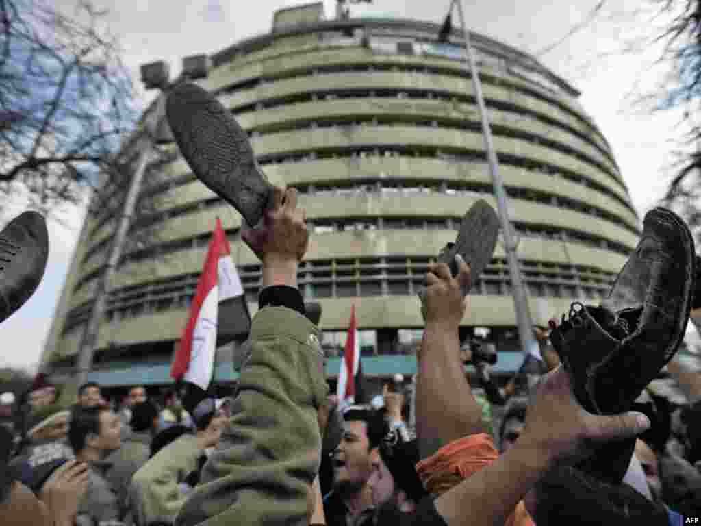 Antigovernment protestors demonstrate by raising their shoes in front of state TV in Cairo on February 11.