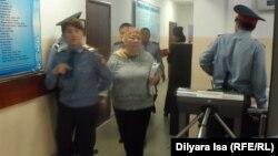 Руководителя общественной организации «Защитим свое жилье» Кыздыгой Ажаркулову (в центре) ведут на заседание суда. Шымкент, 5 апреля 2016 года.