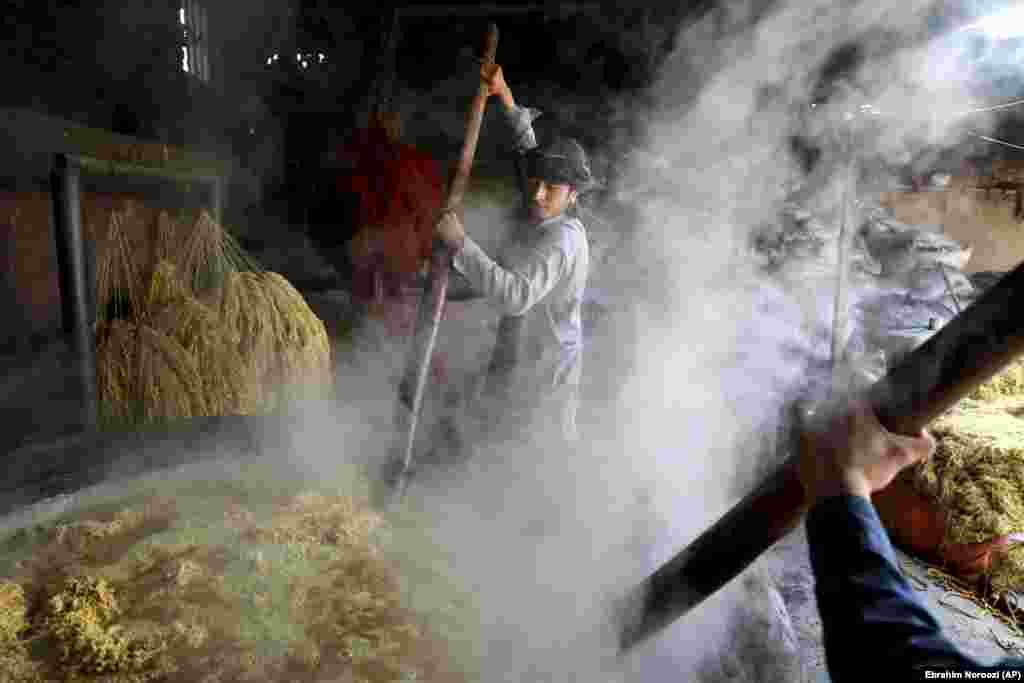 Работнікі мяшаюць воўну ў чане на фарбавальным заводзе ў Кабуле, Аўганістан