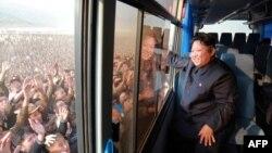 Лідер Північної Кореї Кім Чен Ин вітає з автобуса натовп людей в одному з відбудованих після повені регіонів країни, 8 жовтня 2015 року