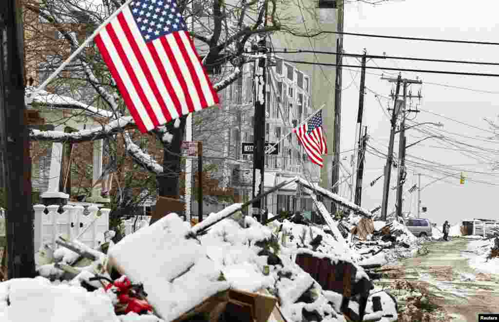 A man stands in a street in New York among piles of debris outside homes due to flooding from superstorm Sandy. The debris is now covered in snow left by a subsequent storm. (Reuters/Lucas Jackson)
