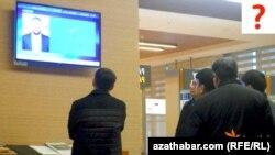 Aşgabadyň aeroportunda telewizora tomaşa edýän ýaşaýjylar.