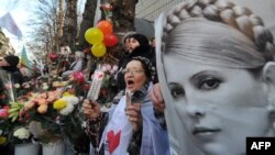 A supporter of Yulia Tymoshenko holds her portrait during a rally in front of the Kyiv 's prison as they mark her 51st birthday