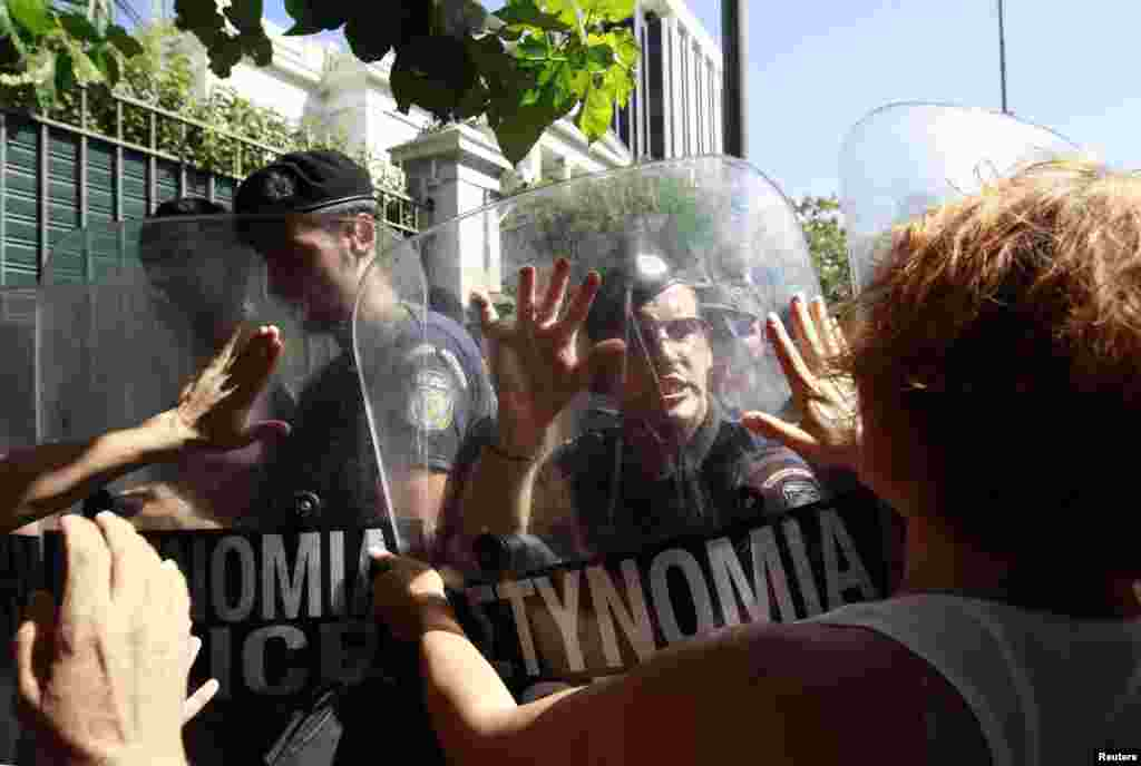 Escorts of people with disabilities try to break through a police blockade outside the Greek parliament during a rally against new austerity measures in Athens on September 27. (REUTERS/John Kolesidis)