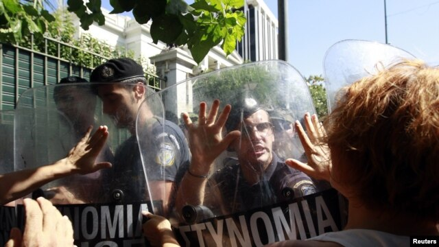 Escorts of people with disabilities try to break through a police formation outside parliament during a rally against new austerity measures in Athens in late September.