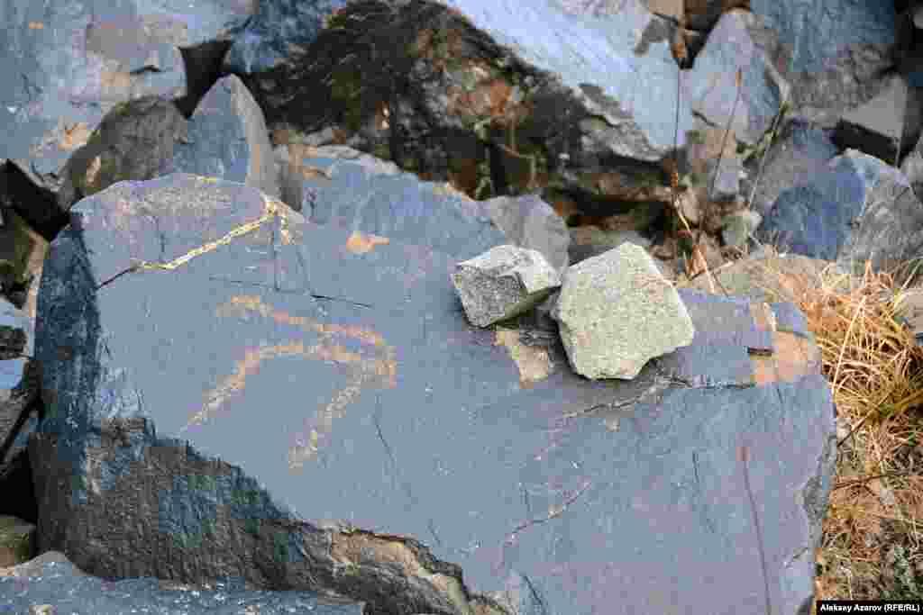 Однако чаще всего петроглифы начинают попадаться на камнях у подножия Кыземшека и в долине ниже нее. Обычно маленькими камнями (турами) на больших камнях горные туристы и альпинисты маркируют тропы, чтобы не сбиться с пути. Здесь же туры сделаны археологами на камнях с наскальными рисунками.
