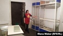 Владелица продовольственного магазина Тамара Цечаева показывает пострадавшие в ходе наводнения стеллажи, витрины и само помещение. Фото сделано в июне 2015 года.