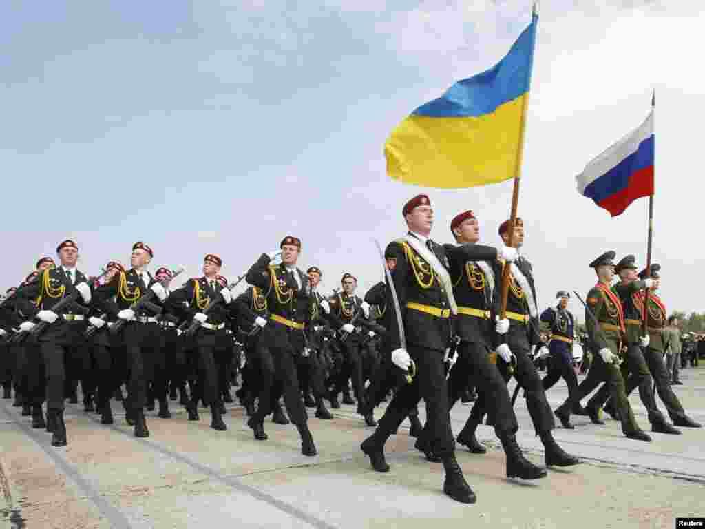 Лава з російських і українських вояків, перед якою несуть прапори обох держав.