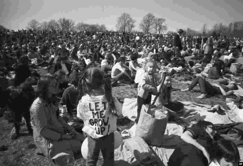 Частина натовпу, що спостерігає за Днем Землі, зокрема, підліток зі знаком «Дозвольте мені вирости» на спині, відпочиває на вершині пагорба в парку Фермаунт у Філадельфії, 23 квітня 1970 року