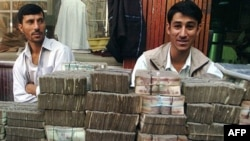 Two money-changers wait for customers at an exchange market in Kabul.