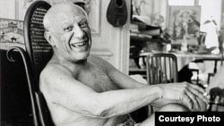 France -- Pablo Picasso laughing in his favorite rocking chair, 1957