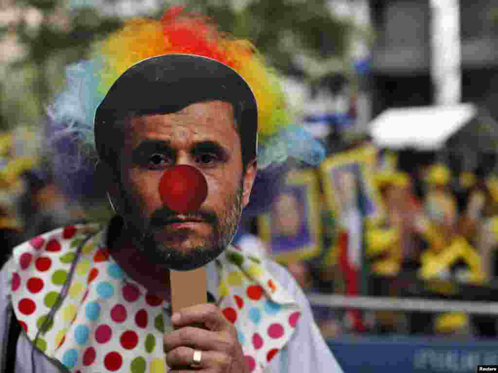 A demonstrator wears a mask depicting Iranian President Mahmud Ahmadinejad during a protest outside  UN headquarters in New York on September 22. (Photo taken by Eduardo Munoz for Reuters)