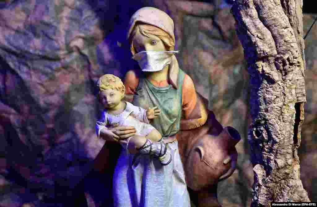 Рождественские ясли со статуэткой Девы Марии в защитной маске были установлены в Кафедральном соборе Турина, Италия, 3 декабря 2020 года