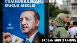 A woman walks by an election-campaign poster for Turkish President Recep Tayyip Erdogan in Istanbul earlier this week.