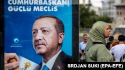 Женщина рядом с агитационным постером действующего президента и кандидата в президенты Турции Реджепа Тайипа Эрдогана. Стамбул, 18 июня 2018 года.