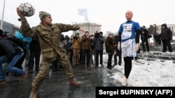 "A Ukrainian serviceman throws a ball at a mannequin depicting Russian President Vladimir Putin dressed in a soccer uniform during a ""Stop Putin. Stop war"" rally in January."