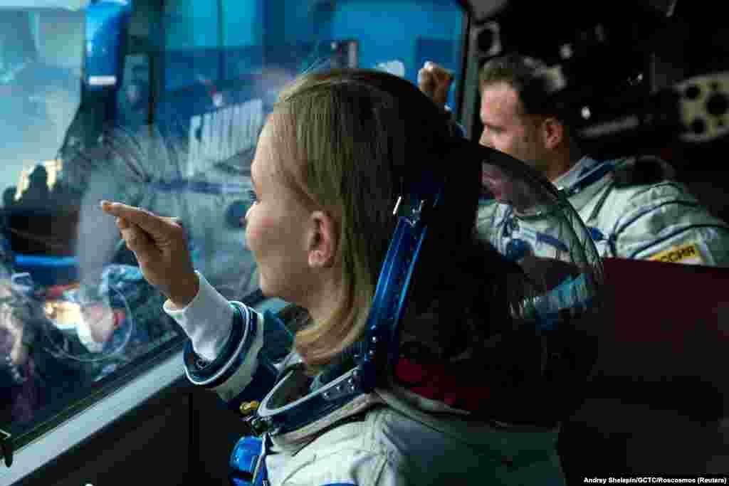 Actrița rusă, Yulia Peresild, gesticulează într-un autobuz în timp ce se îndreaptă către nava spațială Soyuz MS-19. Nava spațială a fost lansată de la Cosmodromul Baikonur din Kazahstan cu o echipă de filmare la bord, pentru realizarea unei scene dintr-un film pe Stația Spațială Internațională.