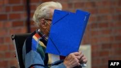 Йозеф С. прикрива лицето си в началото на първото заседание по делото му в Бранденбург, 7 октомври 2021 г.