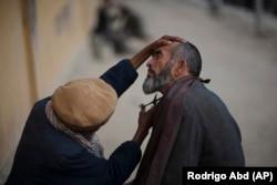 A roadside barber trims a customer's beard at a street shop in Kabul in 2010.