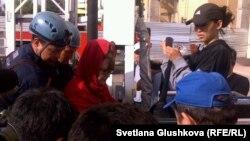 Багжан Аязбекова (в центре в красном платке) и ее сноха Гулим Бабакова (справа) спущены на землю в люльке спасательного устройства после семи суток акции протеста на строительном кране. Астана, 4 июня 2013 года.