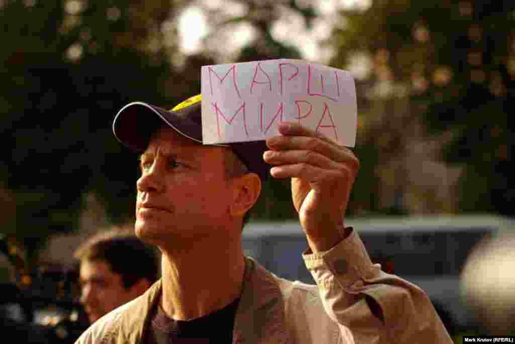 """Участники акции держали в руках небольшие листочки бумаги с надписями """"Марш мира"""" - это и послужило одной из формальных причин для их задержания полицией"""