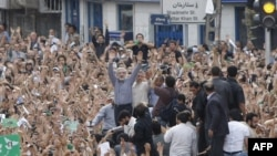 Mir Hossein Musavi (C) raises his arms as he appears at an opposition protest in Tehran, 15Jun2009