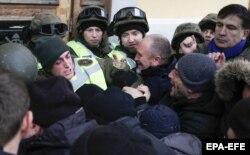 Міхеїл Саакашвілі (праворуч) спостерігає, як мітингувальники, яких він закликав йти до Жовтневого палацу, під час штурму будівлі виривають бійця Нацгвардії зі строю перед центральним входом до будівлі. Київ, 17 грудня 2017 року