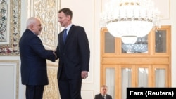 Iranian Foreign Minister Mohammad Javad Zarif (left) shakes hands with British Foreign Secretary Jeremy Hunt, in Tehran, November 19, 2018