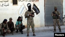 Syrian rebel fighters pose near Islamic State calligraphy and drawings in Dabiq after capturing the city on October 16.