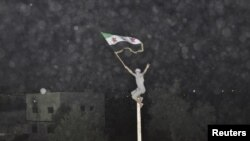 Syria -- A demostrator holds an opposition flag during a protest against regime at Kfr Suseh area in Damascus, 02Jul2012