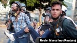 Представители СМИ несут на руках пострадавшего в ходе демонстрации коллегу. Каракас, 1 мая 2019 года.