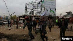 Afghan police and officials carry body parts away from the scene of a suicide attack in Kabul blamed on the Taliban.