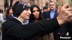 A young fan takes a selfie with Kim Kardashian during her visit to Yerevan in 2015.